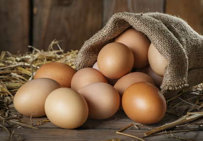 Raw organic farm eggs, straw on the old wooden background