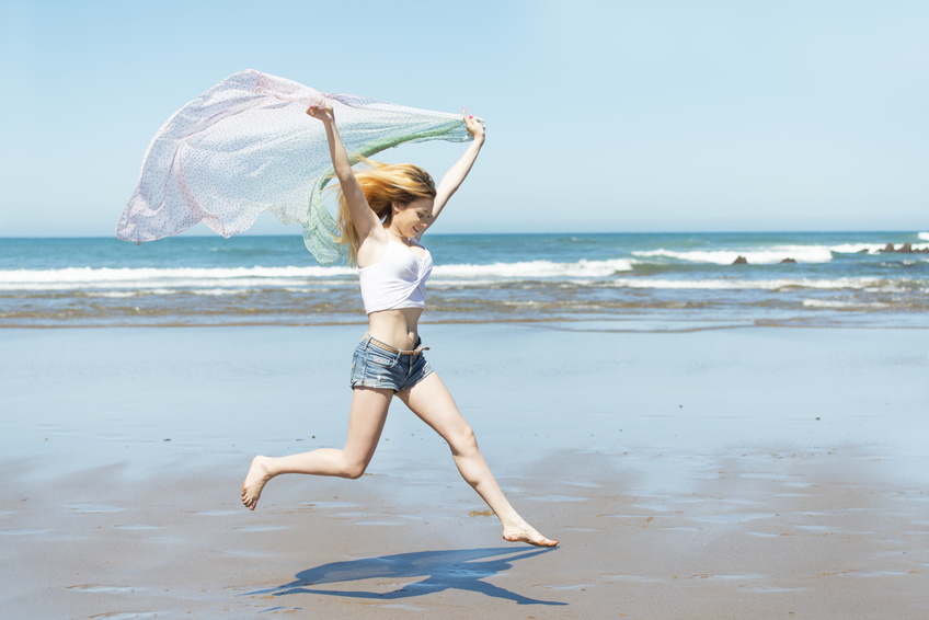 Woman running down the beach in summer season.